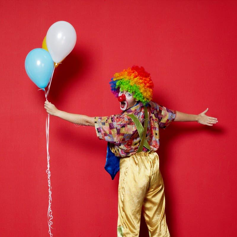 Clown mit Ballonen auf rotem Hintergrund stockfoto