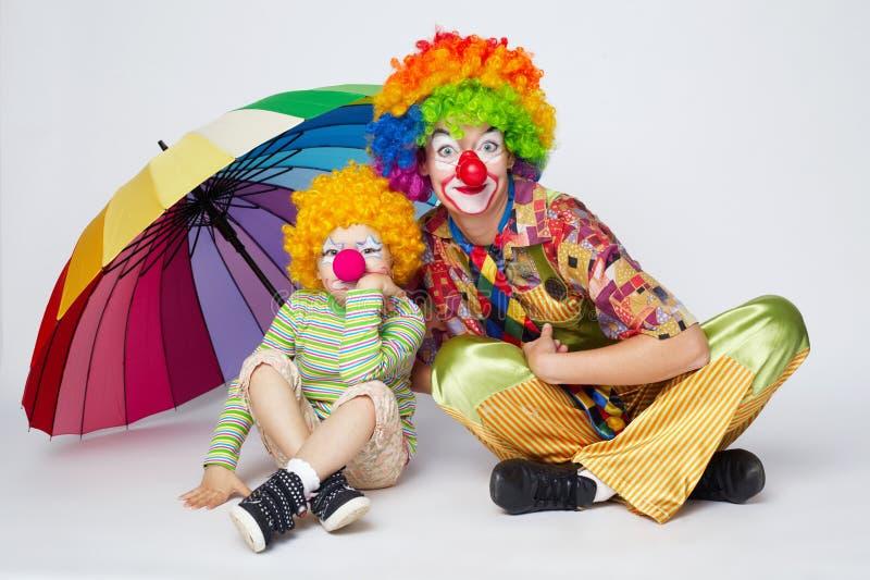 Clown mit buntem Regenschirm auf Weiß lizenzfreies stockfoto