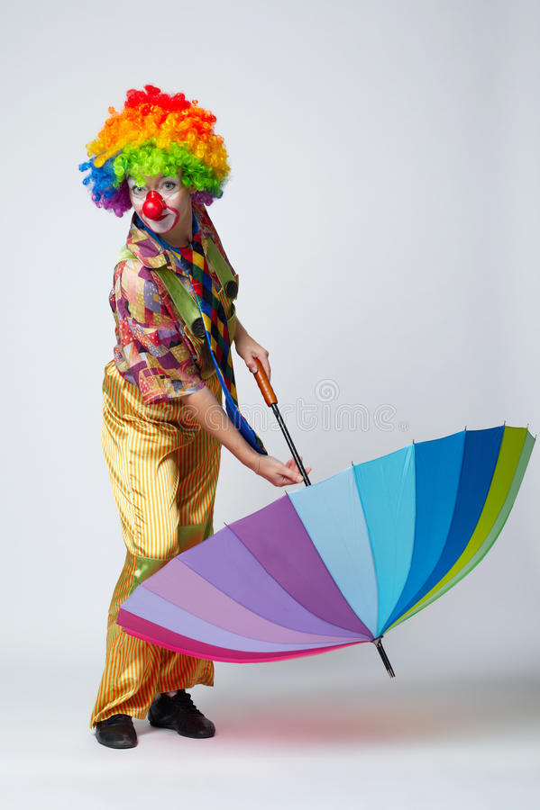 Clown mit buntem Regenschirm auf Weiß stockbild