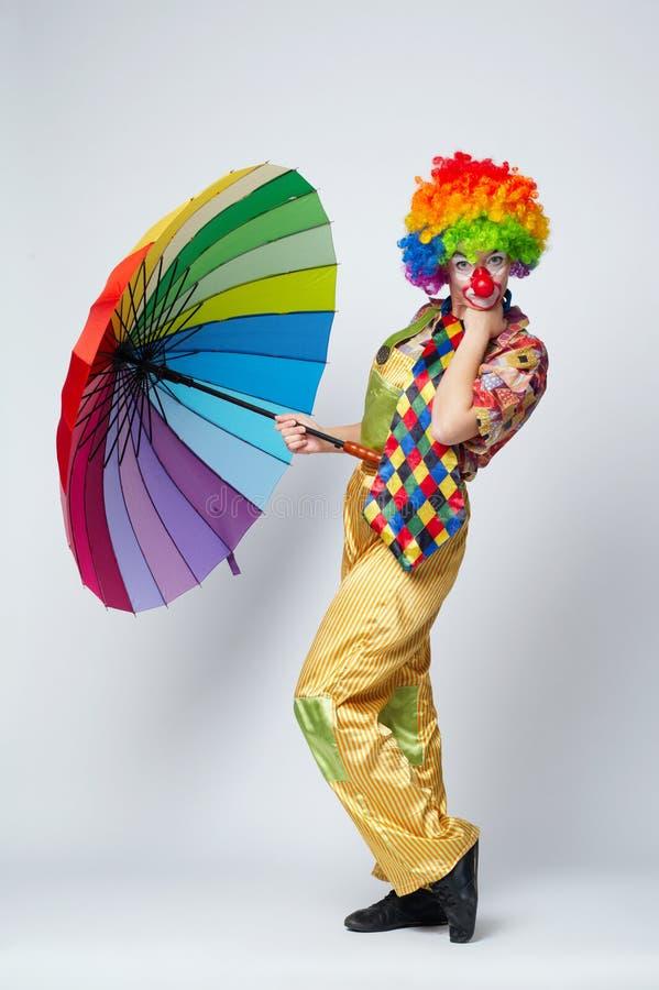 Clown mit buntem Regenschirm auf Weiß lizenzfreie stockfotos