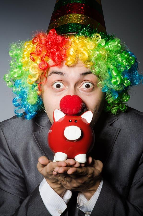 Clown mit piggybank lizenzfreie stockbilder