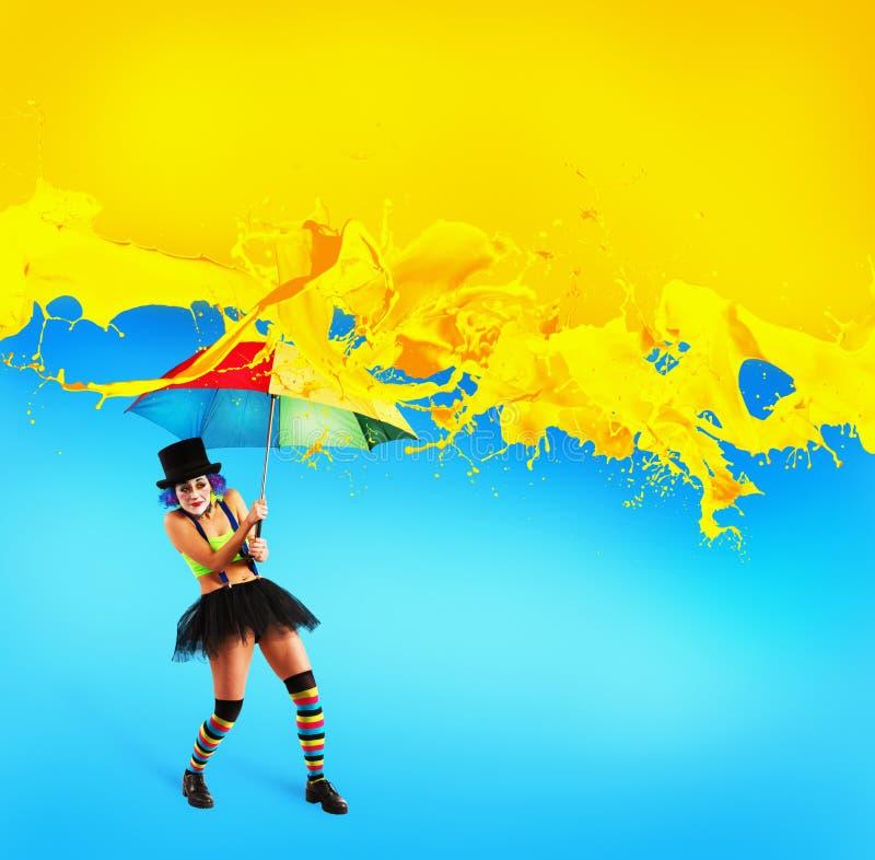 Clown mit Regenschirm bedeckt sich von den gelben Farbtropfen stockfoto