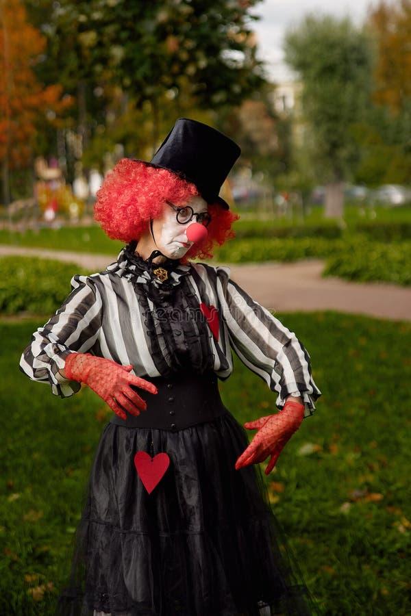 Clown na peruca vermelha com no parque fotografia de stock royalty free