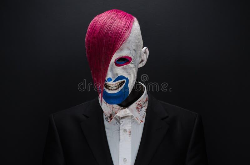 Clown- och allhelgonaaftontema: Läskig clown med rosa hår i ett svart omslag med godisen i hand på en mörk bakgrund i studion royaltyfri fotografi