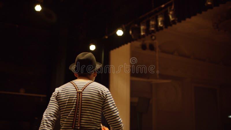 Clown på etapp Tillbaka sikt av clownen med paraplyet i hans händer i randig t-skjorta och hatten som ut bakifrån kommer platser royaltyfri foto