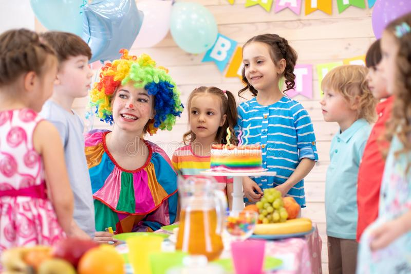 Clown playing with children. Kids group celebrate birthday at table. Holiday in a children`s club. stock photo