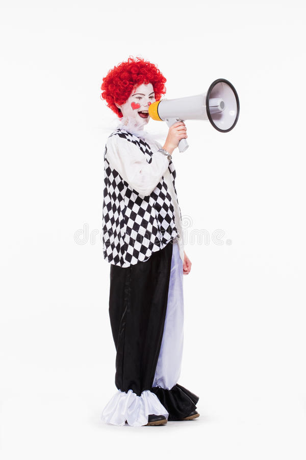 Clown in Red Wig and Makeup Using Megaphone. stock photo
