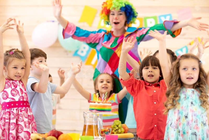Clown som spelar med barn Ungegruppen firar födelsedag och poserar för kameraanseende på tabellen Ferie i barn royaltyfri fotografi