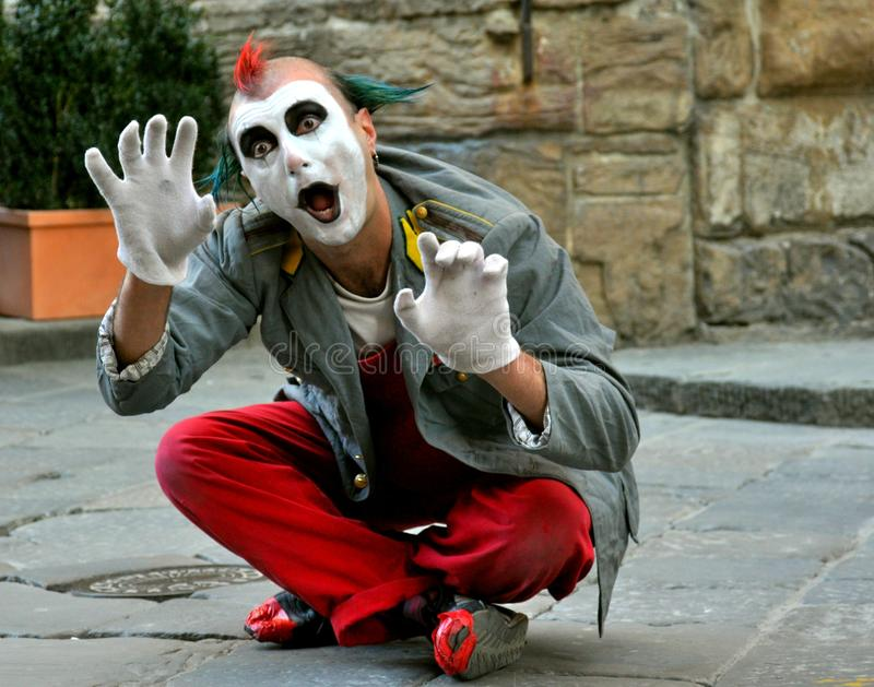 Clown street artist in Italy. Street artist in Florence , Italy.Funny , happy clown male doing a show on the streets. mime actor royalty free stock images
