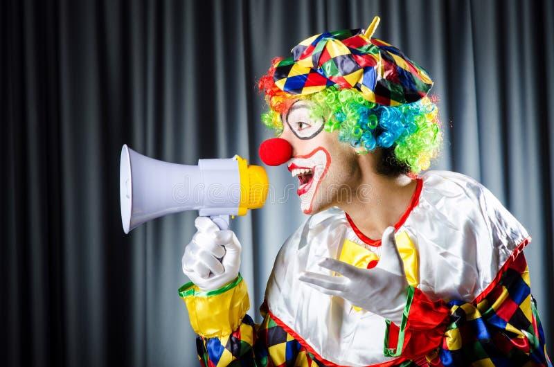 Clown in studio with loudspeaker. On black stock photo