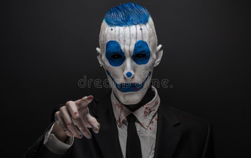 Clown terrible et thème de Halloween : Clown bleu fou dans le costume noir d'isolement sur un fond foncé dans le studio photographie stock