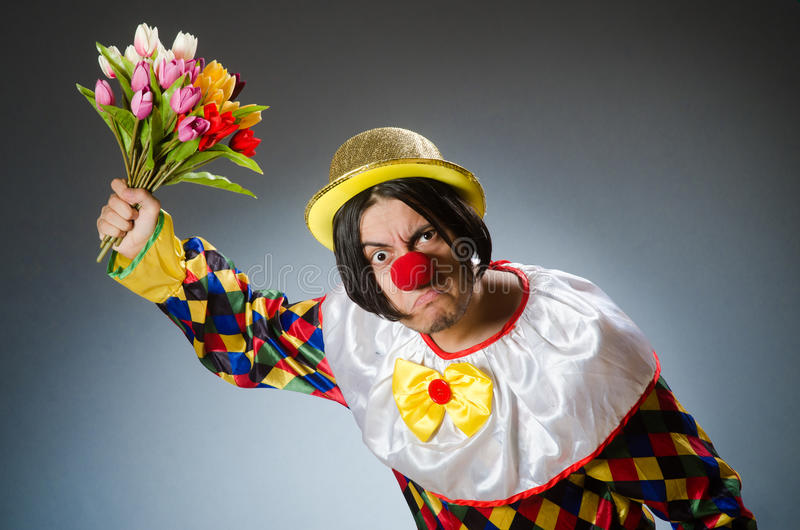 Clown with tulip flowers in funny concept. The clown with tulip flowers in funny concept stock photography