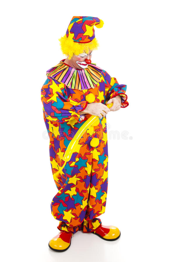 Clown Twisting Balloon Animal. Clown twisting a balloon into the shape of an animal. Full body isolated stock images