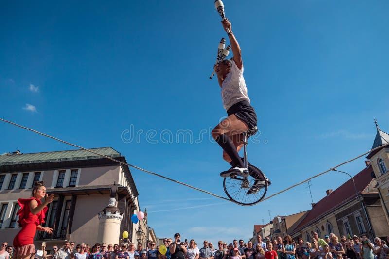 Clown und Akrobat Reitenbicykle auf Seil während UFO-Straßenfests - internationale Sitzung von Straßenausführenden und -schauspie stockfotografie