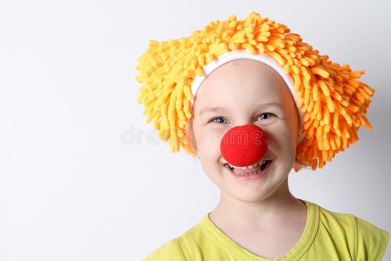 Clownen behandla som ett barn flickan med en röd näsa i ett roligt lock arkivfoton