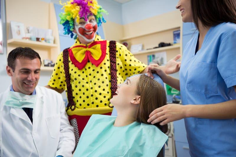 Clownen i tand- klinik gör skrattunga flickan royaltyfri foto