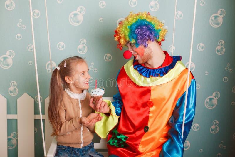 Clownen inviterar lilla flickan att äta födelsedagkakan royaltyfri foto
