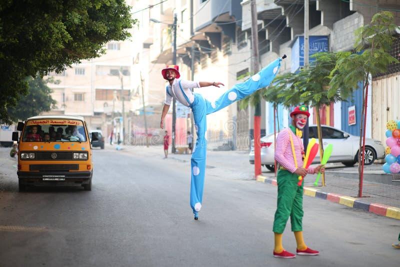 Clowner sedd växelverkan med barn i Gaza, Palestina arkivbilder