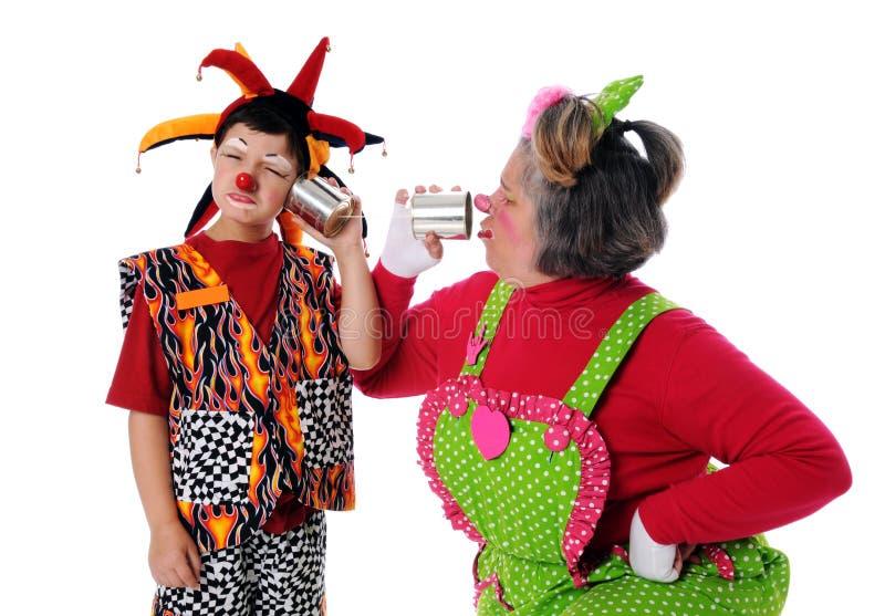 Clowns à l'aide des téléphones de boîte en fer blanc photo stock