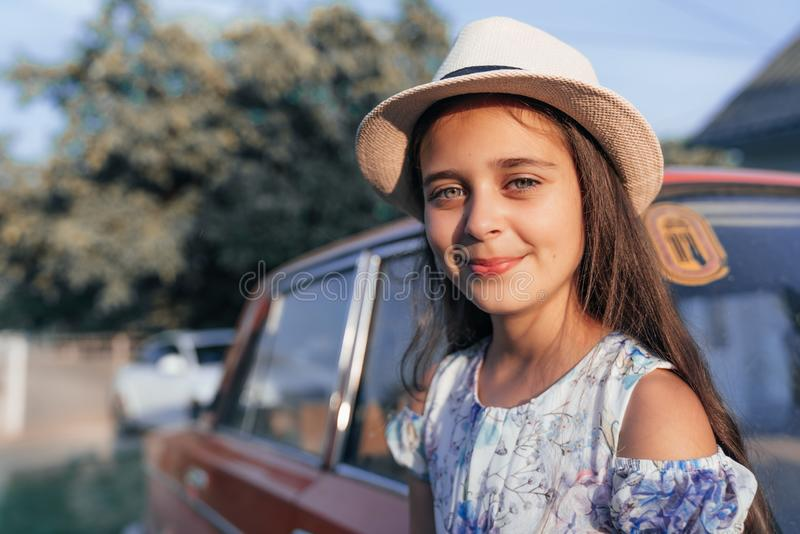 Clsose up portrait, beautiful young brunette little girl in dress and hat leaned on the red old antique car and looking royalty free stock image