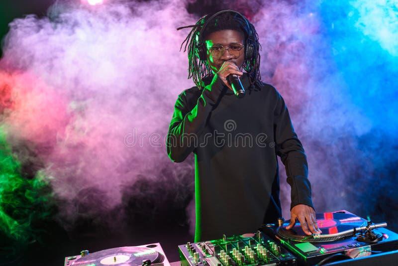club afroamericano profesional DJ con el mezclador y el micrófono de los sonidos imagen de archivo