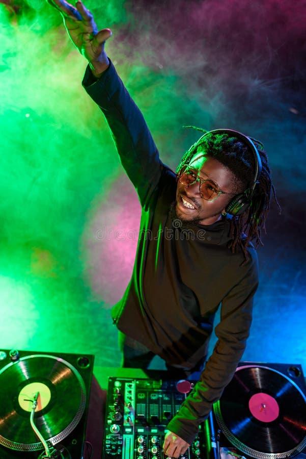 club afroamericano profesional DJ en auriculares con el mezclador de sonidos imagen de archivo libre de regalías