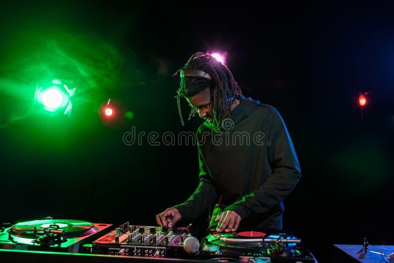 club afroamericano profesional DJ en auriculares con el mezclador de sonidos foto de archivo libre de regalías