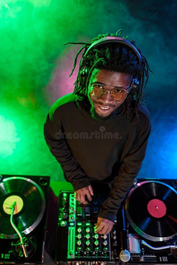 club afroamericano profesional DJ en auriculares con el mezclador de sonidos imagenes de archivo