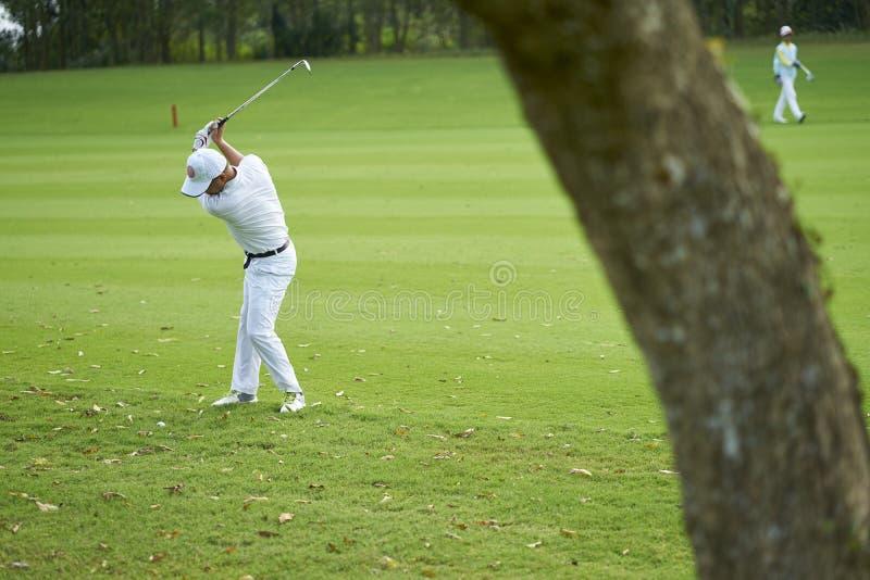 Club de balanceo del golfista asiático para un movimiento en campo de golf foto de archivo