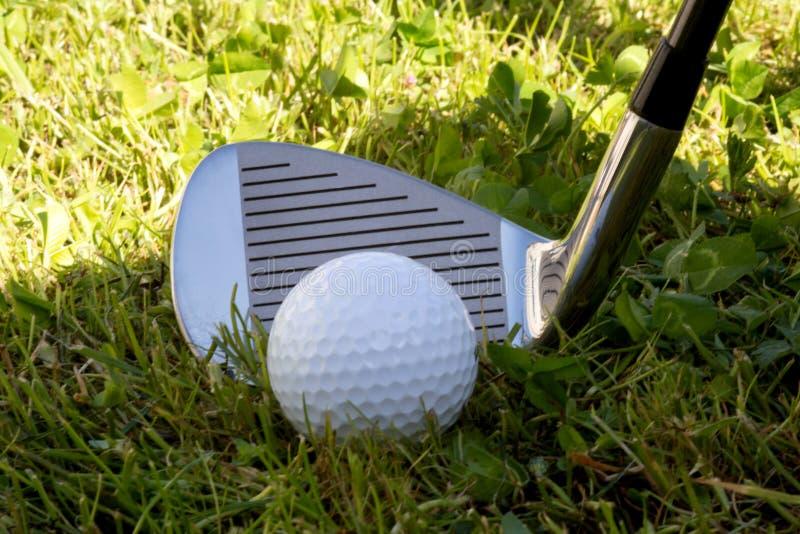 Club de fer de golf et boule de golf dans l'herbe rugueuse photos stock