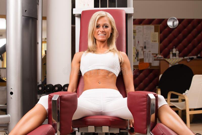 Club de fitness del gimnasio interior con las mujeres jovenes que entrenan a pesos con las piernas imágenes de archivo libres de regalías