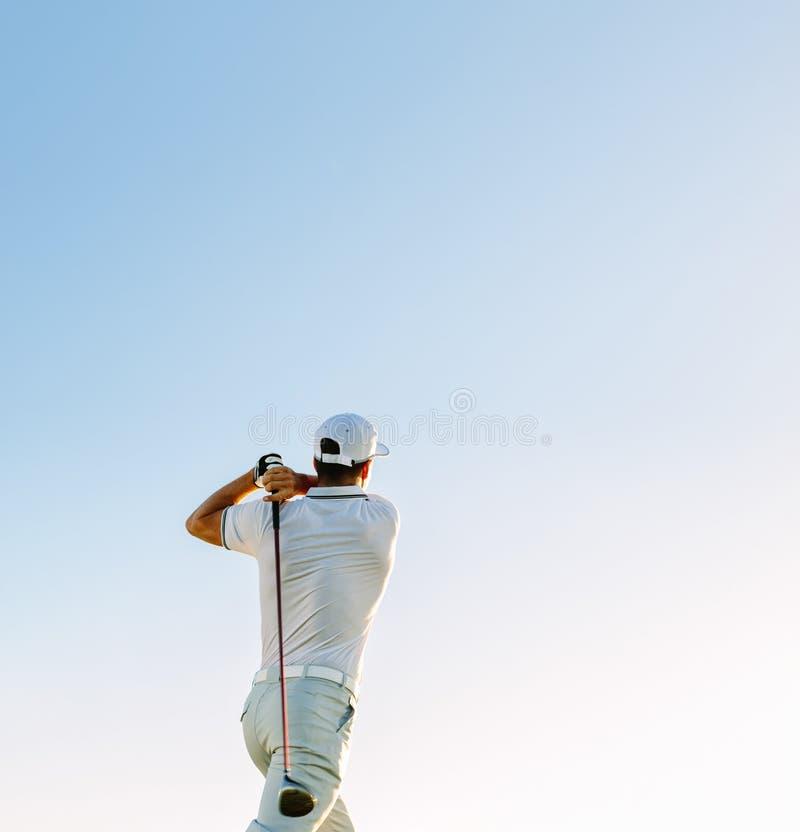 Club de golf de balanceo del hombre contra el cielo claro foto de archivo libre de regalías