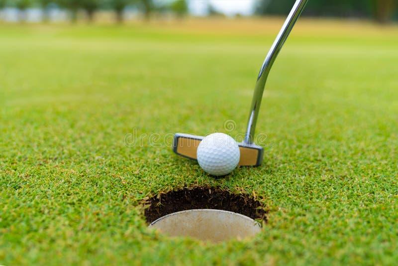 Club de golf y bola en hierba, club de golf y cierre de la pelota de golf para arriba en campo de hierba con puesta del sol imagen de archivo