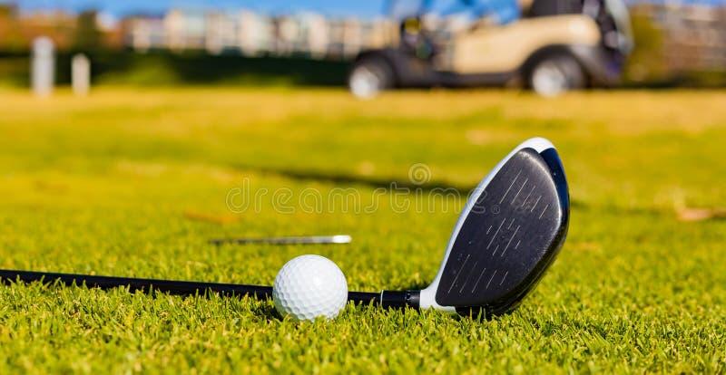 Club di golf e palle su un campo da golf immagini stock