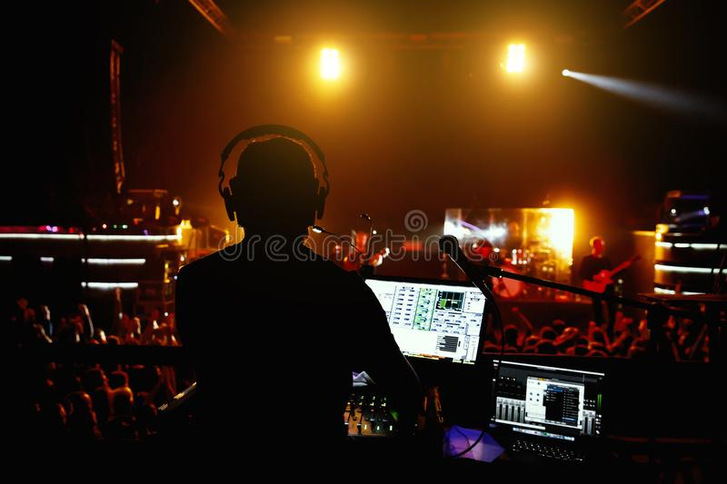 Club, disco DJ playing and mixing music for crowd of happy people. stock photos