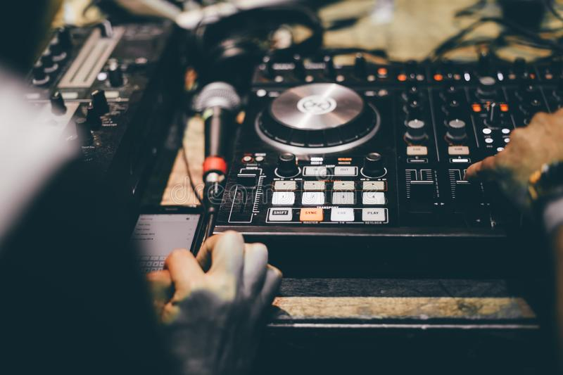 Club DJ playing mixing music on vinyl turntable at party royalty free stock photo