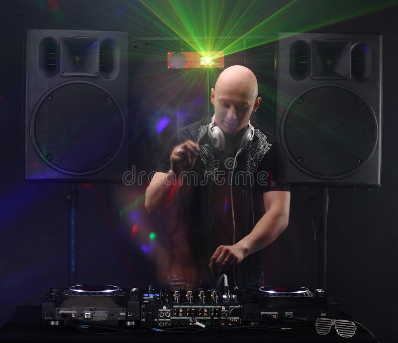 Club DJ with white headphones playing mixing music on turntable and dancing at party. Loudspeakers and lasers on background. slow royalty free stock photo