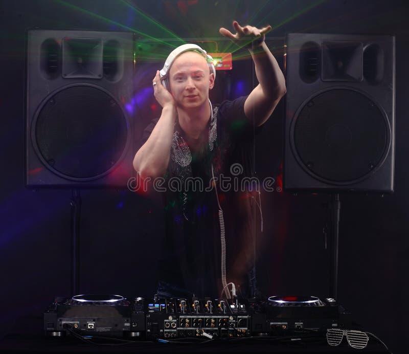 Bold Adult DJ Stands Near Mixer Between Two Big Speakers