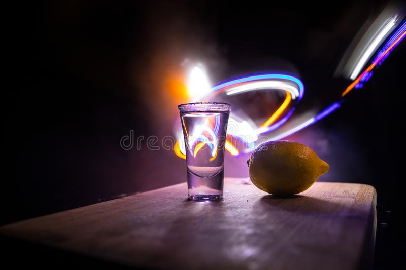 Club drink concept. Tasty alcohol drink cocktail tequila with lime and salt on vibrant dark background or glasses with tequila at. A bar. Selective focus royalty free stock images