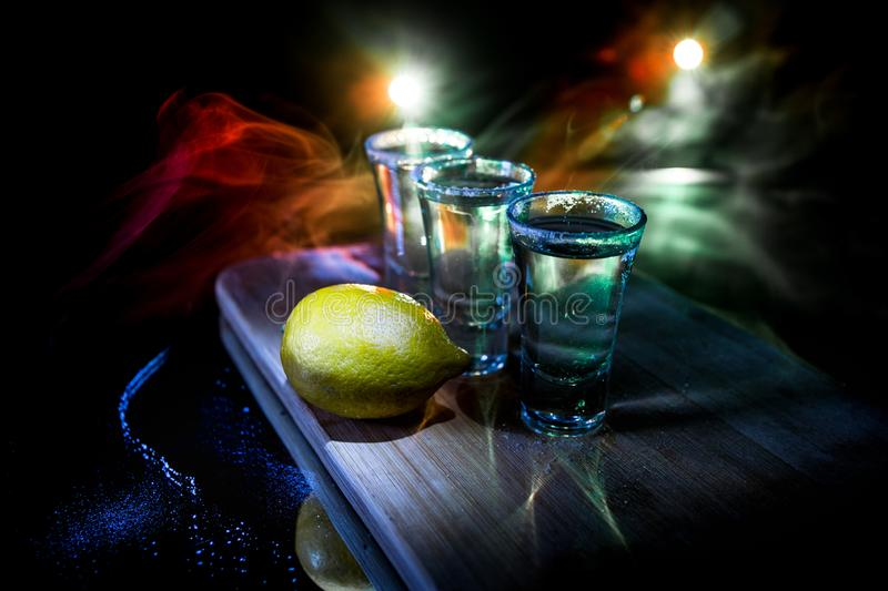 Club drink concept. Tasty alcohol drink cocktail tequila with lime and salt on vibrant dark background or glasses with tequila at. A bar. Selective focus royalty free stock image