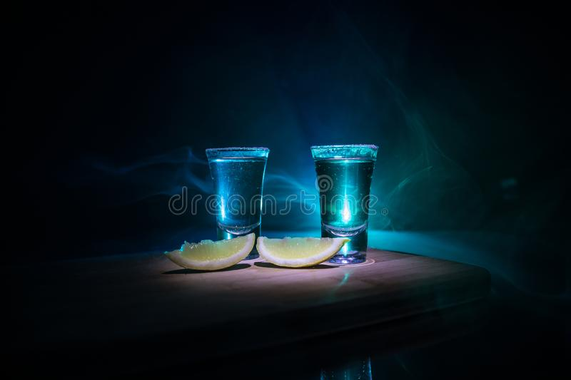 Club drink concept. Tasty alcohol drink cocktail tequila with lime and salt on vibrant dark background or glasses with tequila at. A bar. Selective focus royalty free stock photos