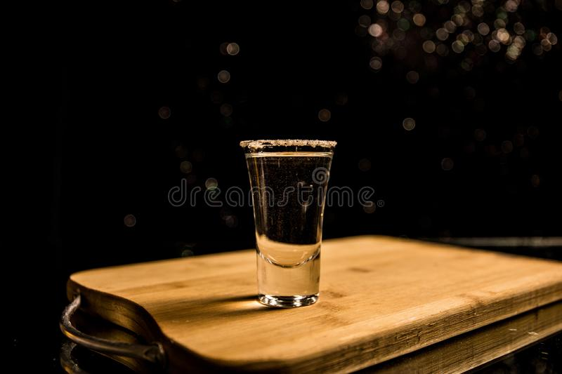 Club drink concept. Tasty alcohol drink cocktail tequila with lime and salt on vibrant dark background or glasses with tequila at. A bar. Selective focus stock images