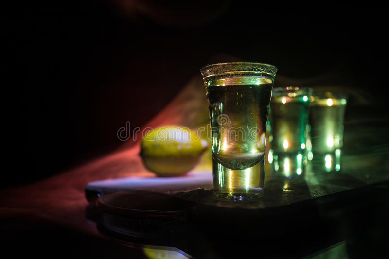 Club drink concept. Tasty alcohol drink cocktail tequila with lime and salt on vibrant dark background or glasses with tequila at. A bar. Selective focus royalty free stock photo