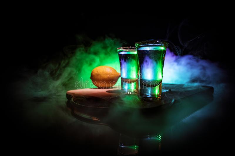 Club drink concept. Tasty alcohol drink cocktail tequila with lime and salt on vibrant dark background or glasses with tequila at. A bar. Selective focus royalty free stock photography