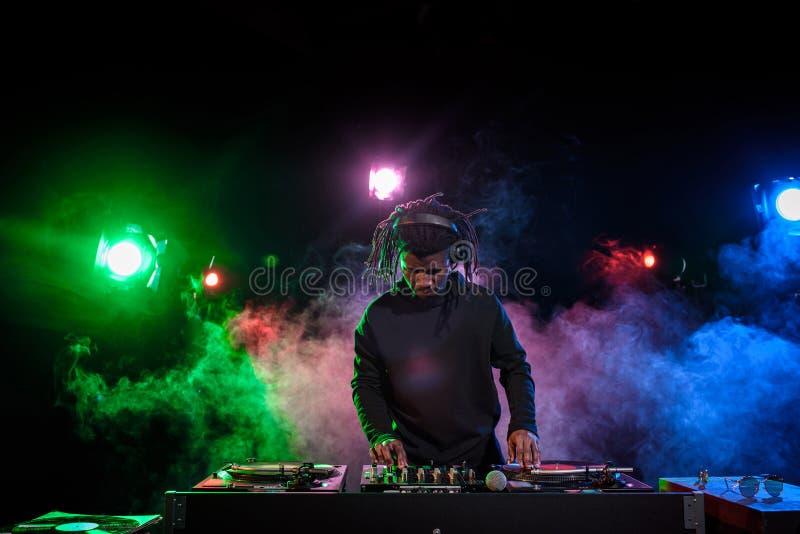 club professionnel DJ d'afro-américain dans des écouteurs avec le mixeur son photo libre de droits