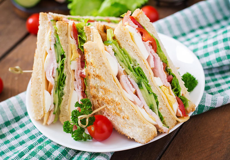 Club sandwich. With cheese, cucumber, tomato, ham and eggs stock image
