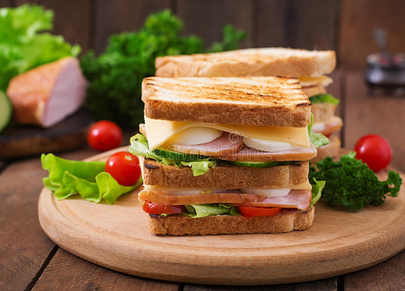 Club sandwich. With cheese, cucumber, tomato, ham and eggs stock photo
