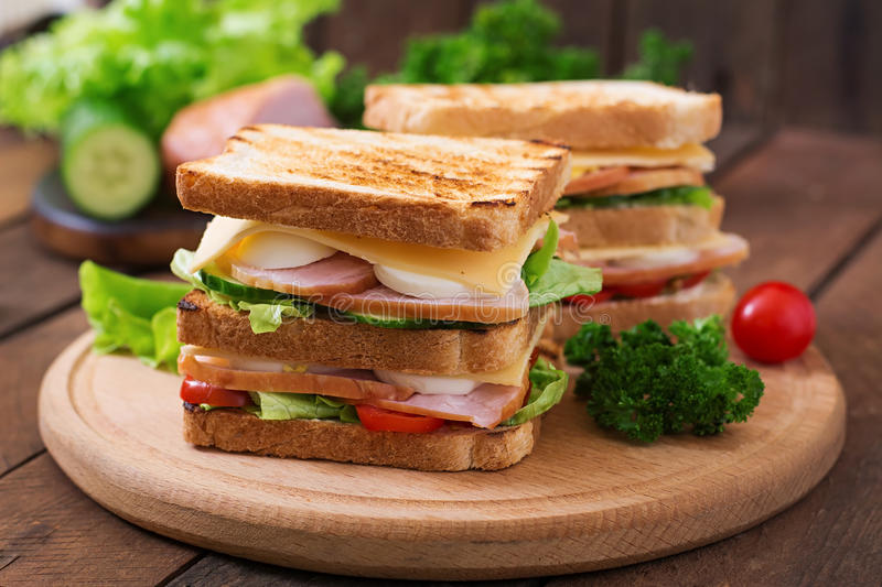 Club sandwich. With cheese, cucumber, tomato, ham and eggs royalty free stock photography