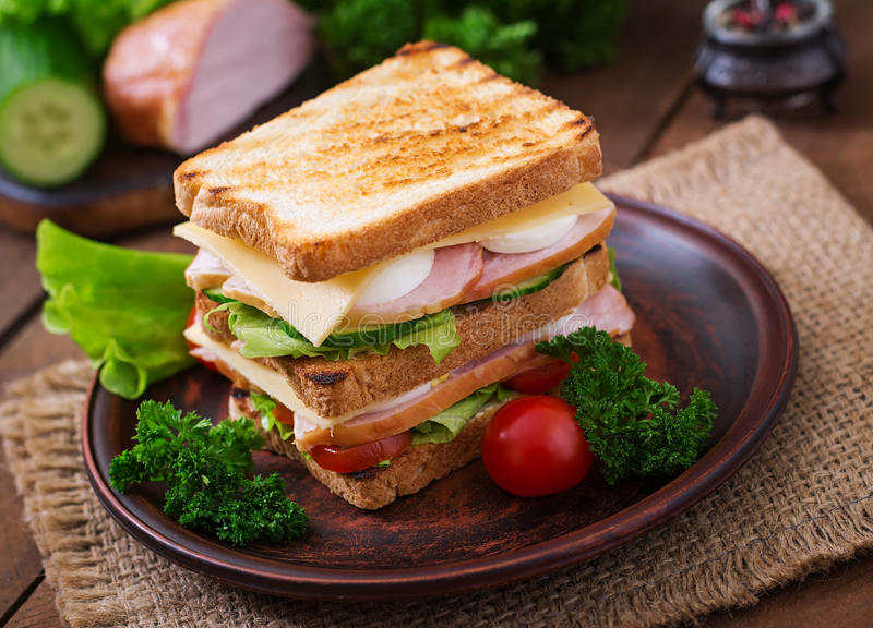 Club sandwich. With cheese, cucumber, tomato, ham and eggs royalty free stock photos