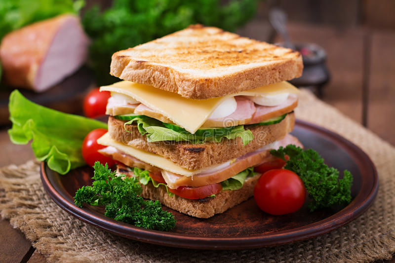 Club sandwich. With cheese, cucumber, tomato, ham and eggs royalty free stock photo